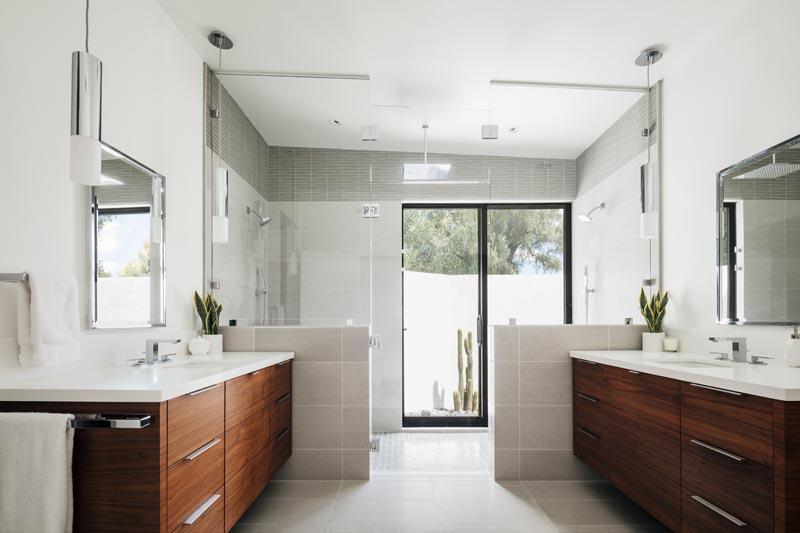 Une salle de bain principale moderne avec des vanités en bois foncé séparées et une grande douche pour deux.