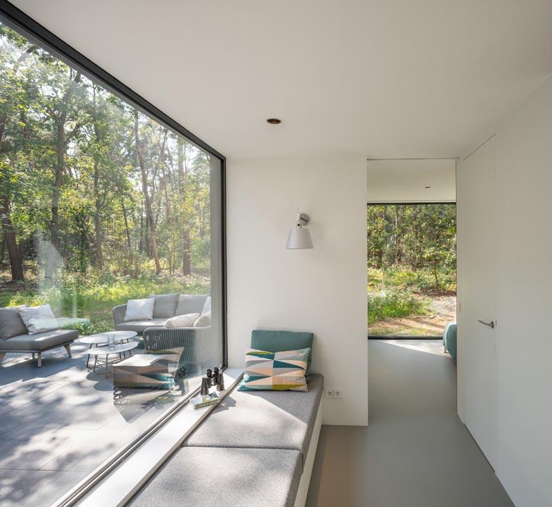 Dans un couloir qui mène à la chambre principale, il y a un siège de fenêtre intégré à côté d'une grande baie vitrée.  #WindowSeat #PictureWindow #HallwayIdeas