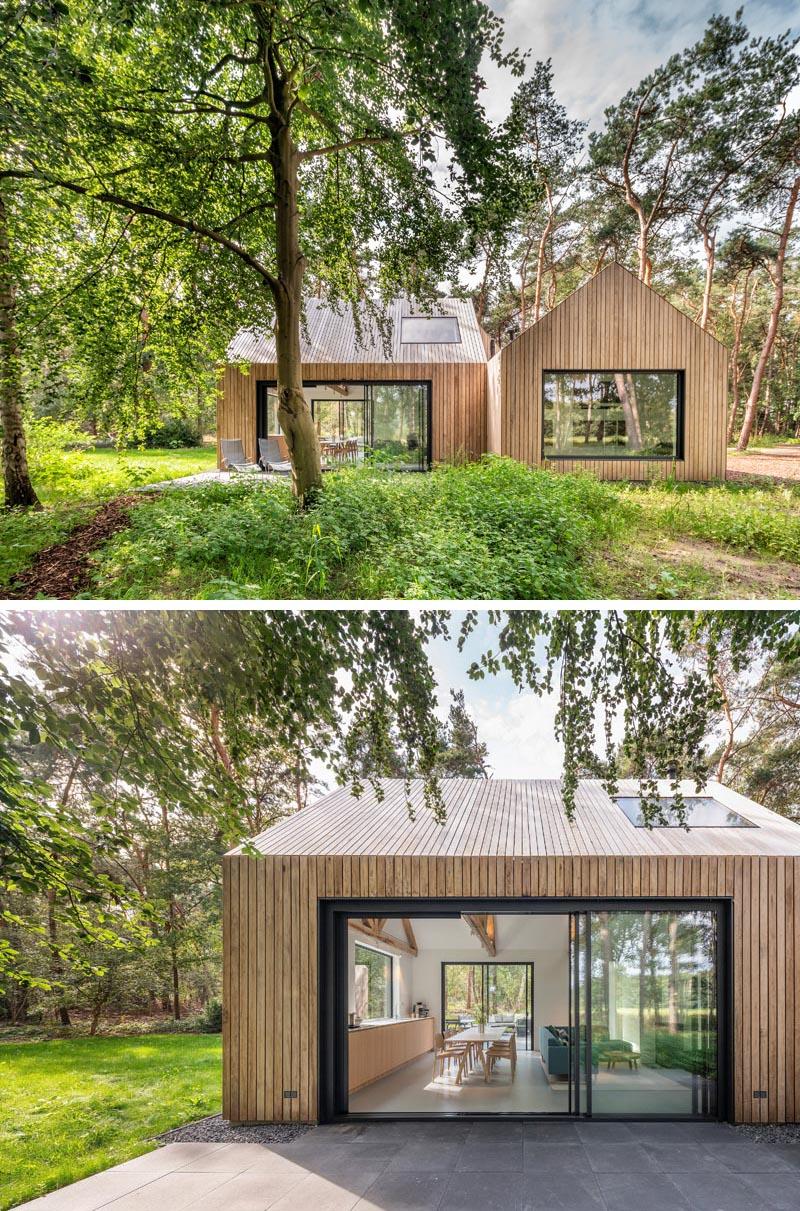 De grandes portes coulissantes en verre à cadre noir relient les terrasses extérieures aux espaces intérieurs de cette maison moderne en bois.  #ModernHouse #WoodHouse #SlidingDoors #BlackFrames