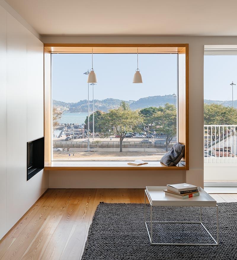 Située dans le salon, cette baie vitrée a un cadre en bois profond, créant un siège de fenêtre assez grand pour que deux personnes puissent s'asseoir et se détendre.  #WindowSeat #PictureWindow #WoodFramedWindowSeat #WindowIdeas #LivingRoom