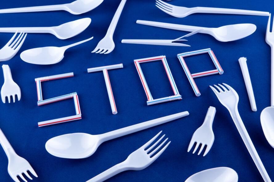 """ustensiles de cuisine en plastique entourant des pailles en plastique disposées pour épeler le mot """"ARRÊTEZ"""""""