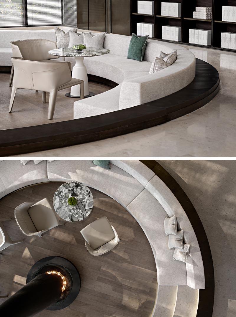 Ce puits de conversation englouti, qui a été conçu comme un espace chaleureux et agréable pour les clients potentiels pour parler, offre des sièges personnalisés qui s'enroulent à l'intérieur de la forme circulaire, avec suffisamment d'espace pour y inclure également de petites tables.  #ConversationPit #SunkenSeating #InteriorDesign #Fireplace