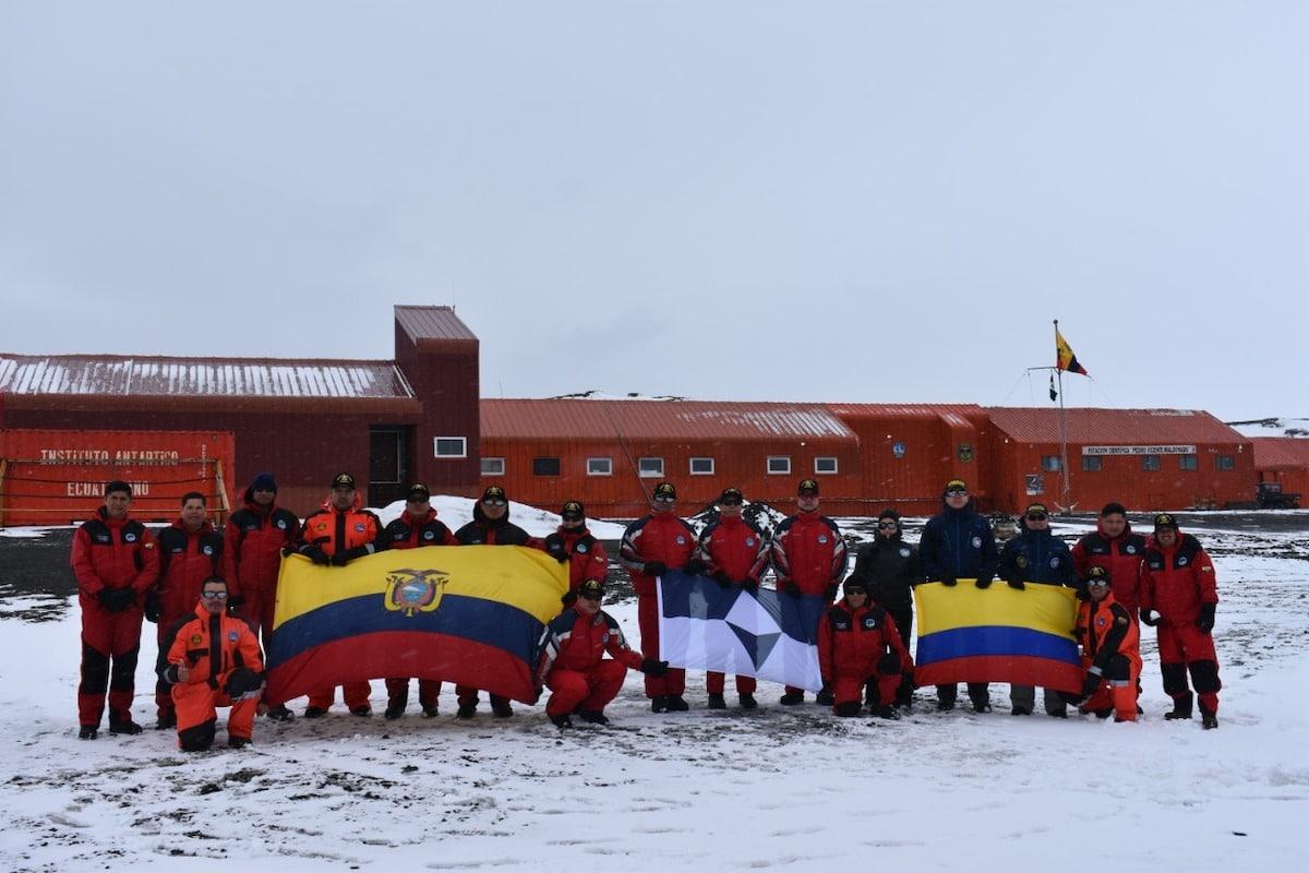Membres des programmes antarctiques nationaux de l'Équateur et de la Colombie avec True South et leurs drapeaux nationaux à la base de Maldonado, en Antarctique